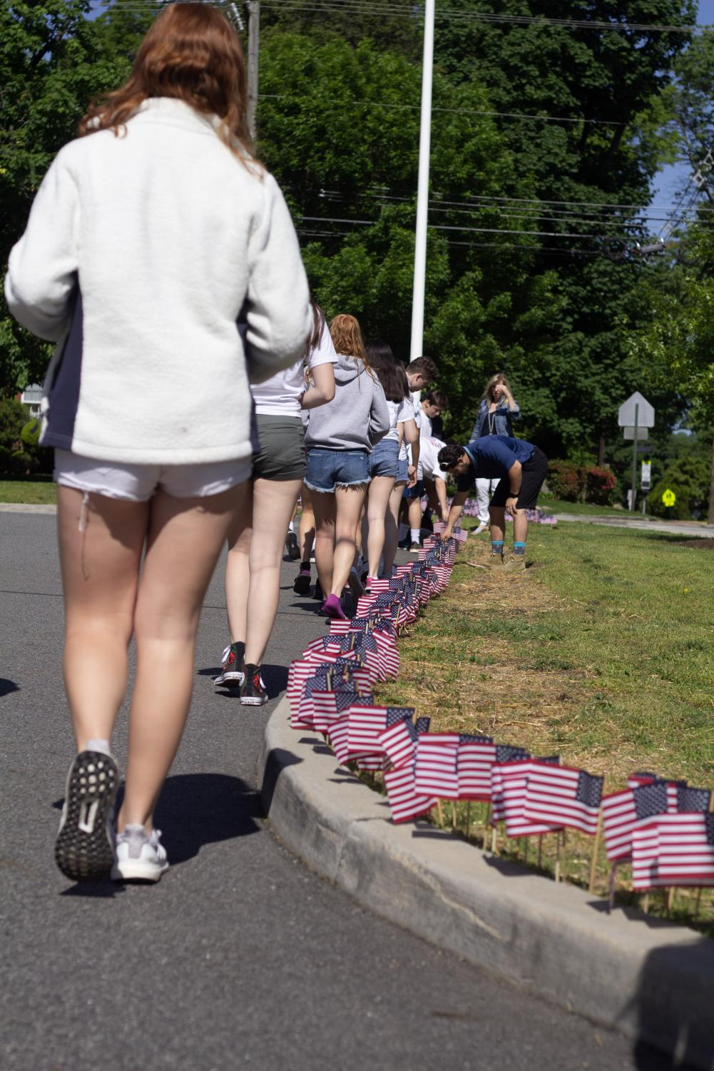 Students place flags in remembrance of soldiers who have served in the US Military.