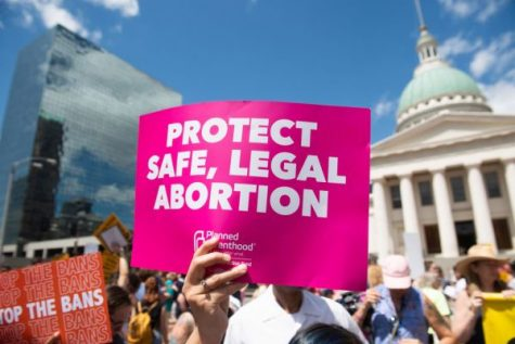 Protesters hold signs as they rally in support of Planned Parenthood and pro-choice and to protest a state decision that would effectively halt abortions by revoking the center